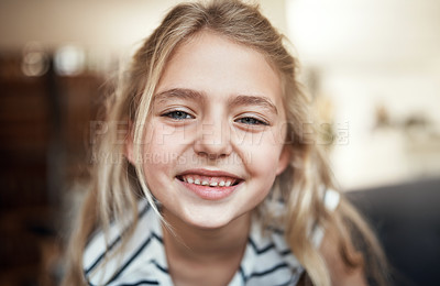 Buy stock photo Cropped portrait of an adorable little girl on a sofa in the living room at home