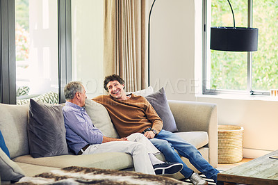 Buy stock photo Shot of a mature man and his elderly father sitting on the sofa at home and chatting