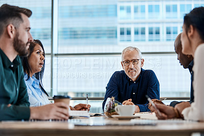 Buy stock photo Shot of a mature businessman discussing ideas with colleagues during a meeting at work
