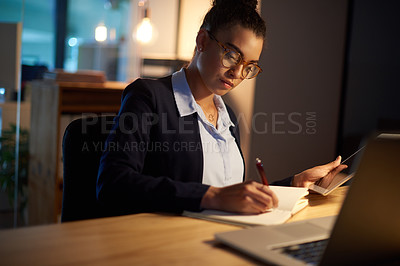 Buy stock photo Shot of a young businesswoman using a digital tablet while writing notes in an office at night