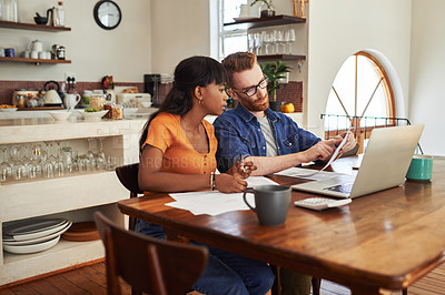 Buy stock photo Cropped shot of a couple looking at paperwork while sitting with their laptop
