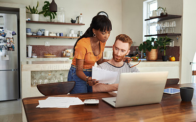Buy stock photo Shot of a man sitting with his laptop and paperwork while his girlfriend stands behind him