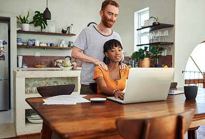 Buy stock photo Shot of a man massaging his girlfriend while she works on her laptop