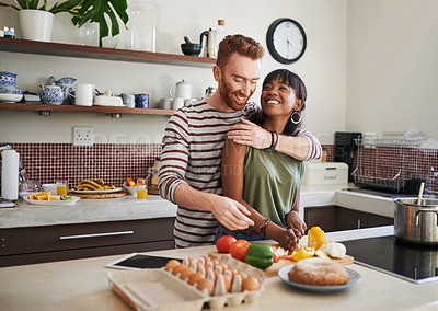 Buy stock photo Shot of a young woman cooking while her boyfriend embraces her from behind