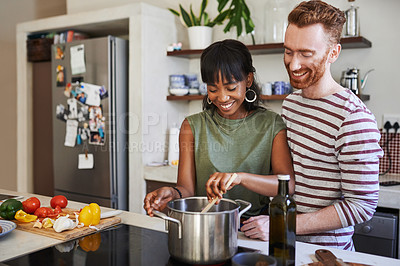 Buy stock photo Shot of a young woman cooking with her boyfriend standing behind her