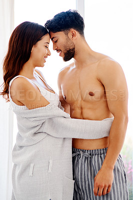 Buy stock photo Shot of a cheerful young couple standing together in their bedroom during the morning hours