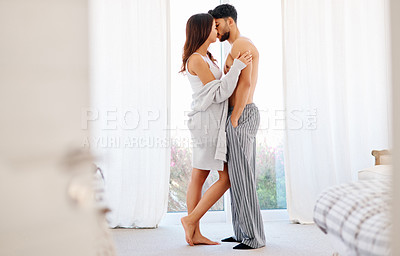 Buy stock photo Shot of a carefree young couple sharing a kiss while standing next to their bedroom window at home