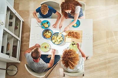 Buy stock photo High angle shot of an affectionate family of four enjoying a meal at a dining table at home