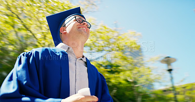 Buy stock photo Cropped shot of a handsome young man posing in his graduation gown and looking away during the day