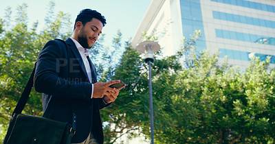 Buy stock photo Cropped shot of a handsome young businessman standing alone and using his cellphone while outside during the day
