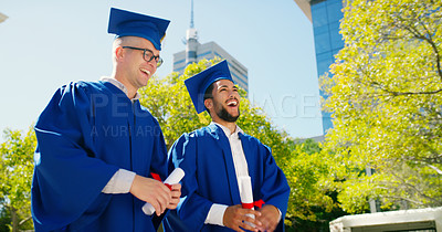 Buy stock photo Cropped shot of two handsome young friends standing together in their graduation gowns and holding their degrees while outside