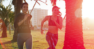 Buy stock photo Cropped shot of two sporty young women out running together