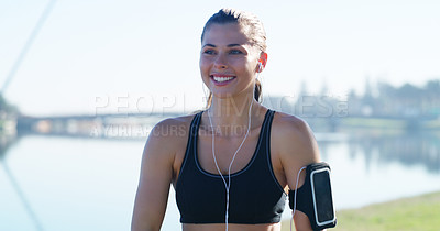 Buy stock photo Cropped shot of a sporty young woman enjoying herself while listening to music