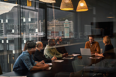 Buy stock photo Cropped shot of a diverse group of businesspeople sitting and having a meeting in a boardroom while in the office