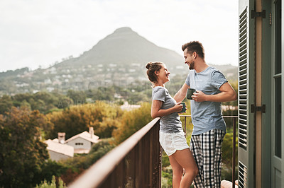 Buy stock photo Shot of an affectionate young couple drinking coffee while standing on their balcony at home in the morning