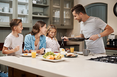 Buy stock photo Cropped shot of a young family having breakfast at home