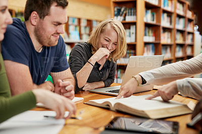 Buy stock photo Shot of a group of young men and women studying together in a library at college