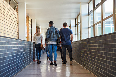 Buy stock photo Rearview shot of a group of young students walking down a hallway together at university