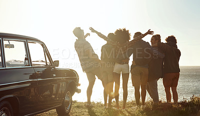 Buy stock photo Full length rearview shot of a diverse young group of friends standing next to a car and facing the ocean