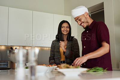 Buy stock photo Shot of a young couple cooking a meal at home