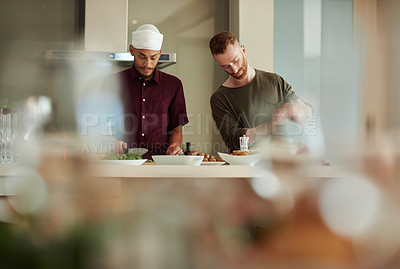 Buy stock photo Shot of two young men cooking a meal at home