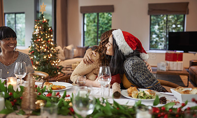Buy stock photo Shot of young friends opening their gifts together while having Christmas lunch at home