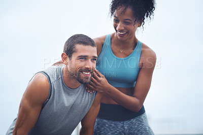 Buy stock photo Shot of a sporty young couple taking a break while exercising outdoors