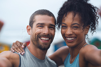 Buy stock photo Portrait of a sporty young couple taking selfies together while exercising outdoors