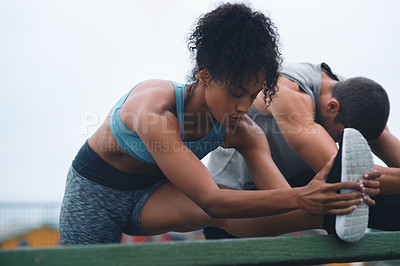 Buy stock photo Shot of a sporty young woman stretching while exercising with her partner outdoors