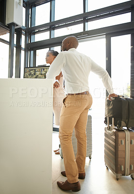 Buy stock photo Full length shot of a happy young couple standing with luggage and checking in at the reception of a hotel