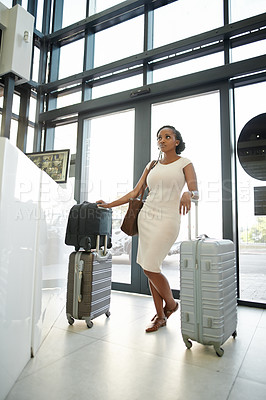 Buy stock photo Full length shot of a beautiful young woman standing with her luggage and checking in at a hotel