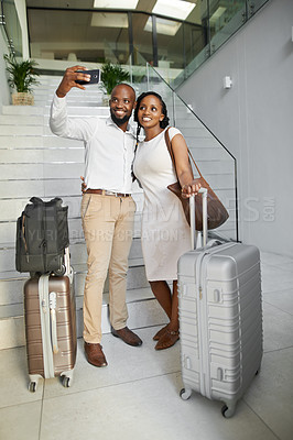 Buy stock photo Full length shot of an affectionate young couple taking selfies with a cellphone while checking in into a hotel