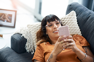 Buy stock photo Cropped shot of a young woman using her cellphone while relaxing on the sofa at home