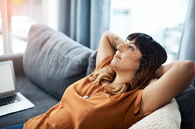 Buy stock photo Cropped shot of a young woman relaxing on the sofa at home