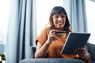 Buy stock photo Shot of a young woman holding her credit card while using a digital tablet