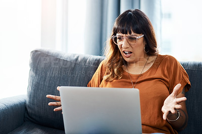 Buy stock photo Shot of a woman looking frustrated while using her laptop at home