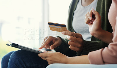 Buy stock photo Cropped shot of two unrecognizable women using a tablet together for online shopping while sitting on the sofa