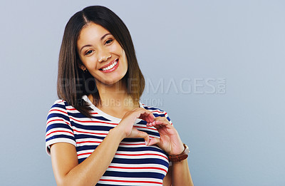 Buy stock photo Studio shot of a young woman making a heart shaped gesture against a grey background