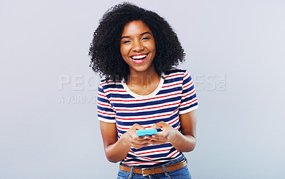 Buy stock photo Studio shot of a beautiful young woman using a smartphone against a grey background