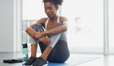 Buy stock photo Full length shot of an attractive young woman taking a break after working out indoors during the day