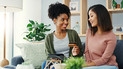 Buy stock photo Cropped shot of two attractive young women using a tablet together for online shopping while sitting on the sofa