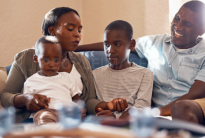 Buy stock photo Cropped shot of a cheerful young family relaxing on a sofa together at home during the day