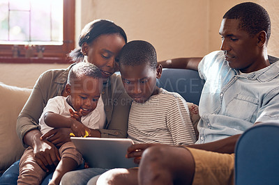 Buy stock photo Cropped shot of a cheerful young family relaxing on a sofa together while browsing on a digital tablet at home during the day