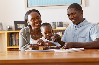Buy stock photo Cropped shot of a couple celebrating their toddler son's birthday with cake inside at home during the day