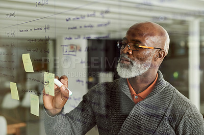 Buy stock photo Cropped shot of a mature businessman brainstorming with notes on a glass wall