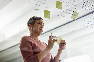 Buy stock photo Cropped shot of a mature businesswoman brainstorming with notes on a glass wall