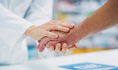 Buy stock photo Cropped shot of a pharmacist holding a patient's hand