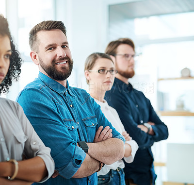 Buy stock photo Portrait of a young businessman standing in a line with his colleagues in an office