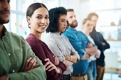 Buy stock photo Portrait of a young businesswoman standing in a line with her colleagues in an office
