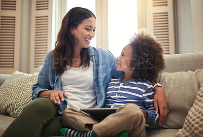 Buy stock photo Shot of young boy using a digital tablet while sitting at home with his mother